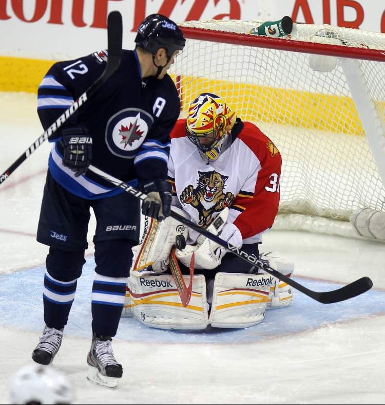 Winnipeg Jets forward Olli Jokinen watches Florida Panthers netminder Scott Clemmensen cover up the puck in the third period Thursday.  (Phil Hossack / Winnipeg Free Press)