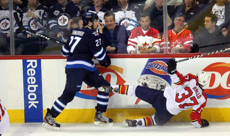 Winnipeg Jets' Eric Tangradi takes Florida Panthers' Greg Rallo out of the play as fans react behind the glass in the third period Thursday.
