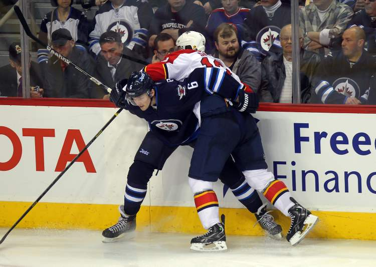 Winnipeg Jets defenceman Ron Hainsey takes Florida Panthers' Jack Skille out of the play in the third period Thursday.  (Phil Hossack / Winnipeg Free Press)