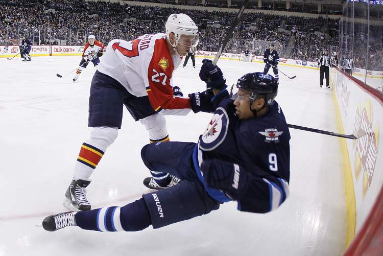 Florida Panthers' Nick Bjugstad checks Winnipeg Jets' Evander Kane during second-period NHL action in Winnipeg Thursday. (JOHN WOODS / THE CANADIAN PRESS)