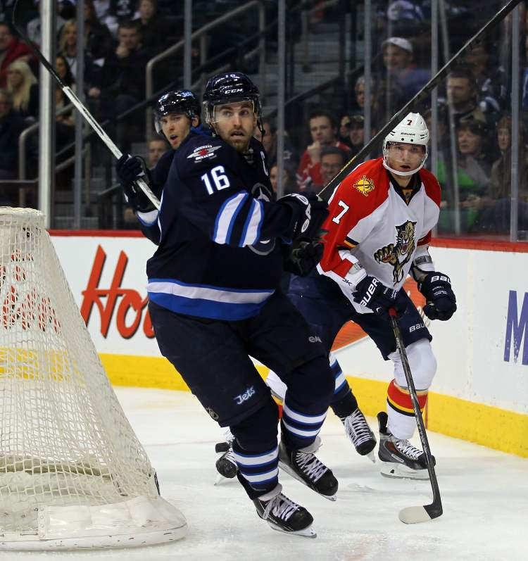 Winnipeg Jets captain Andrew Ladd wheels around Dmitry Kulikov behind the Florida Panthers net in the second period Thursday. S (Phil Hossack / Winnipeg Free Press)