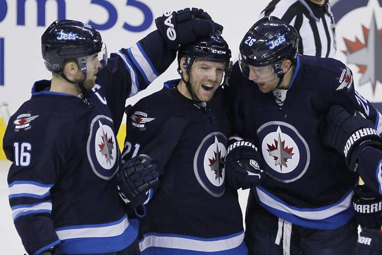 Winnipeg Jets Andrew Ladd (16), Aaron Gagnon (21) and Blake Wheeler (26) celebrate Gagnon's goal against the Florida Panthers during the first period in Winnipeg Thursday.