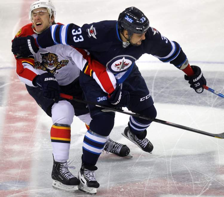 Winnipeg Jets defenceman Dustin Byfuglien pushes Florida Panthers' Shawn Matthias aside as he moves the puck forward Thursday in first-period action. (Phil Hossack / Winnipeg Free Press)