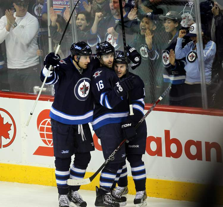 Winnipeg Jets forward Blake Wheeler, captain Andrew Ladd and Bryan Little celebrates Ladd's goal Thursday. (Phil Hossack / Winnipeg Free Press)
