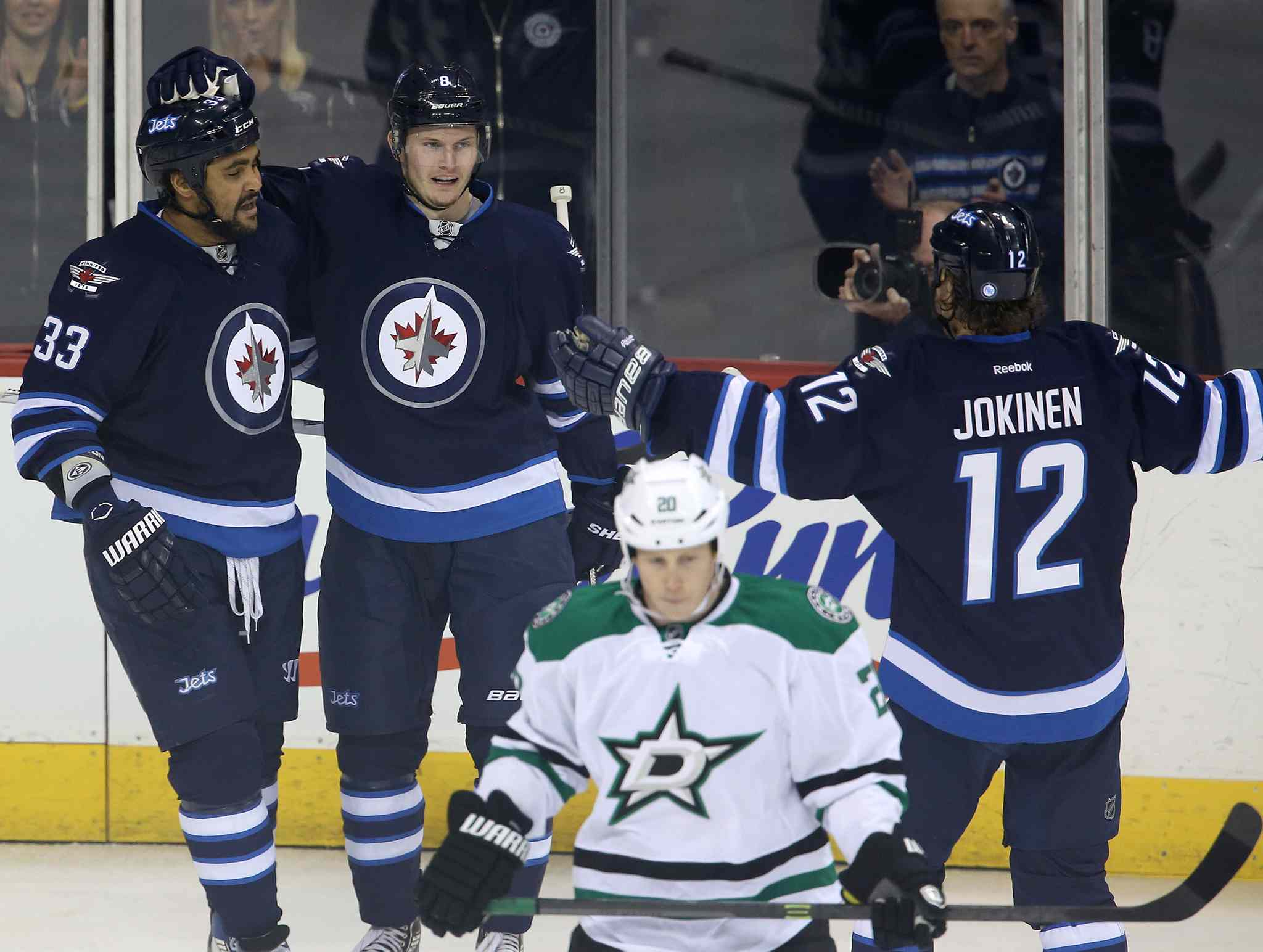 The Winnipeg Jets Dustin Byfuglien (33), Jacob Trouba (centre) and Olli Jokinen celebrate Trouba's goal against the Dallas Stars' as Cody Eakin (20) looks on during the first period.