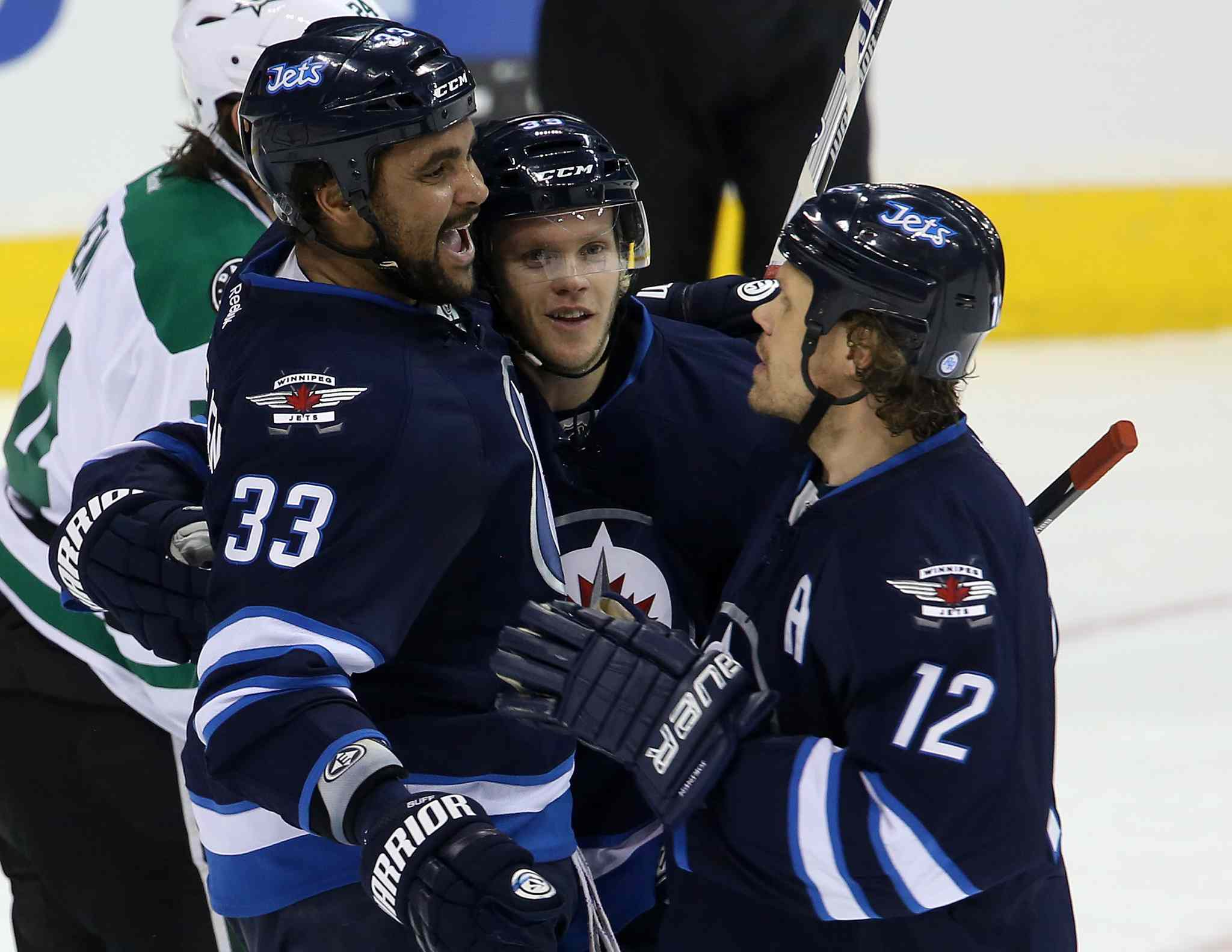 The Winnipeg Jets Dustin Byfuglien (33), Tobias Enstrom (centre) and Olli Jokinen celebrate Enstrom's first-period goal.