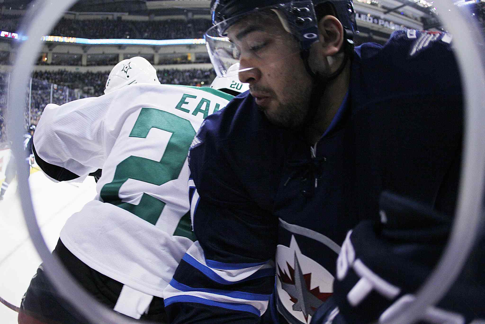 Jets forward Devin Setoguchi gets checked by Stars forward Cody Eakin during second-period NHL action.
