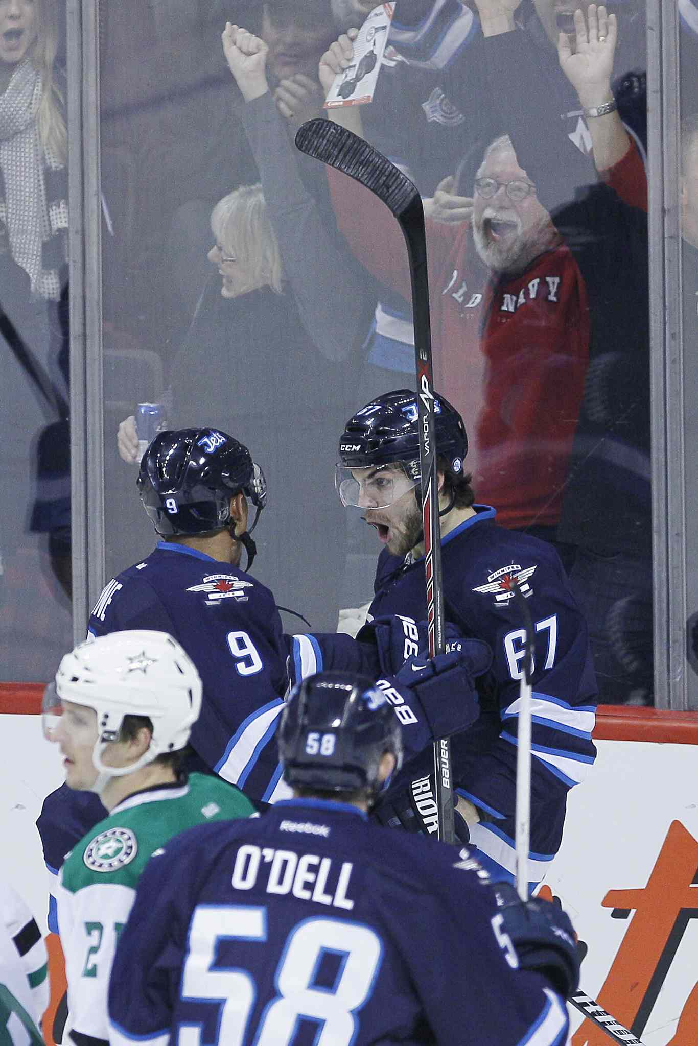 The Winnipeg Jets' Michael Frolik (67), Evander Kane (9) and Eric O'Dell celebrate Frolik's first-period goal.