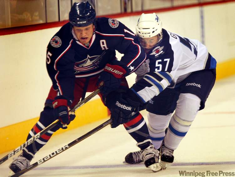 Jets' Jason Gregoire keeps up the defensive action on Blue Jackets'  Derek Dorsett in first-period action Tuesday.