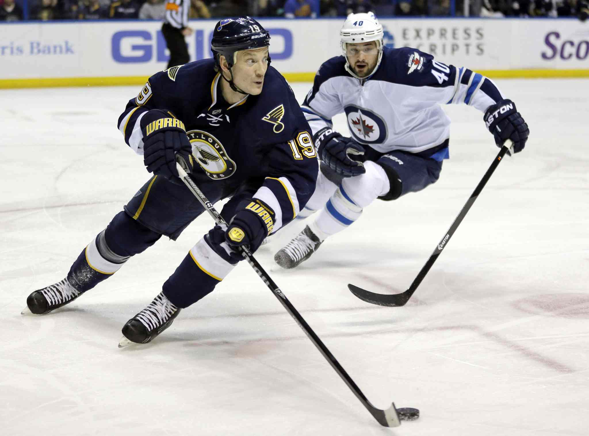 St. Louis Blues' Jay Bouwmeester, left, controls the puck as Winnipeg Jets' Devin Setoguchi gives chase during the first period of Saturday's game.