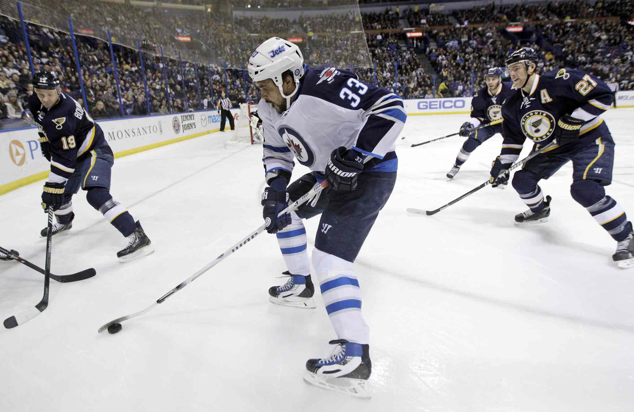Winnipeg Jets' Dustin Byfuglien (33) controls the puck as St. Louis Blues' Jay Bouwmeester (19), Maxim Lapierre (40) and Alex Pietrangelo (27) defend during the first period.