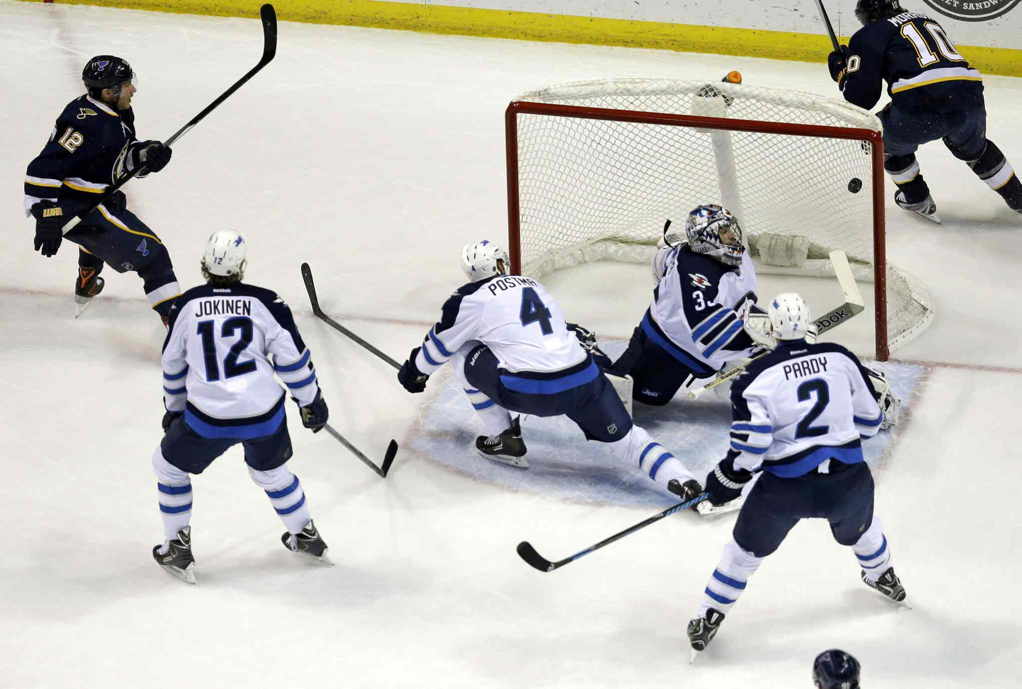 St. Louis Blues' Derek Roy, left, scores a first-period goal past Winnipeg Jets' goalie Al Montoya as Olli Jokinen (12), Paul Postma (4) and Adam Pardy (2) look on.