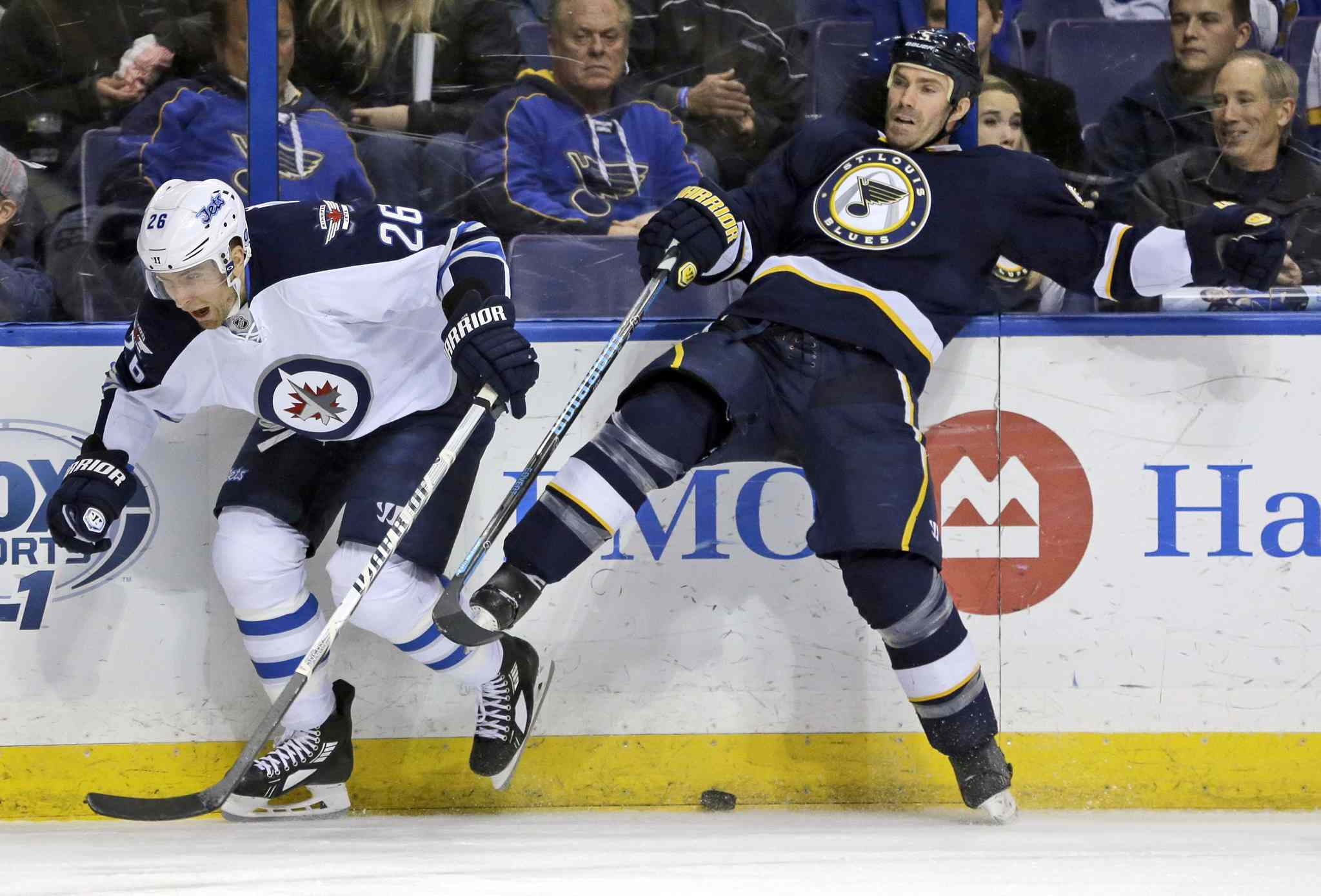 Winnipeg Jets' Blake Wheeler, left, and St. Louis Blues' Barret Jackman collide along the boards while chasing a loose puck during the first period.