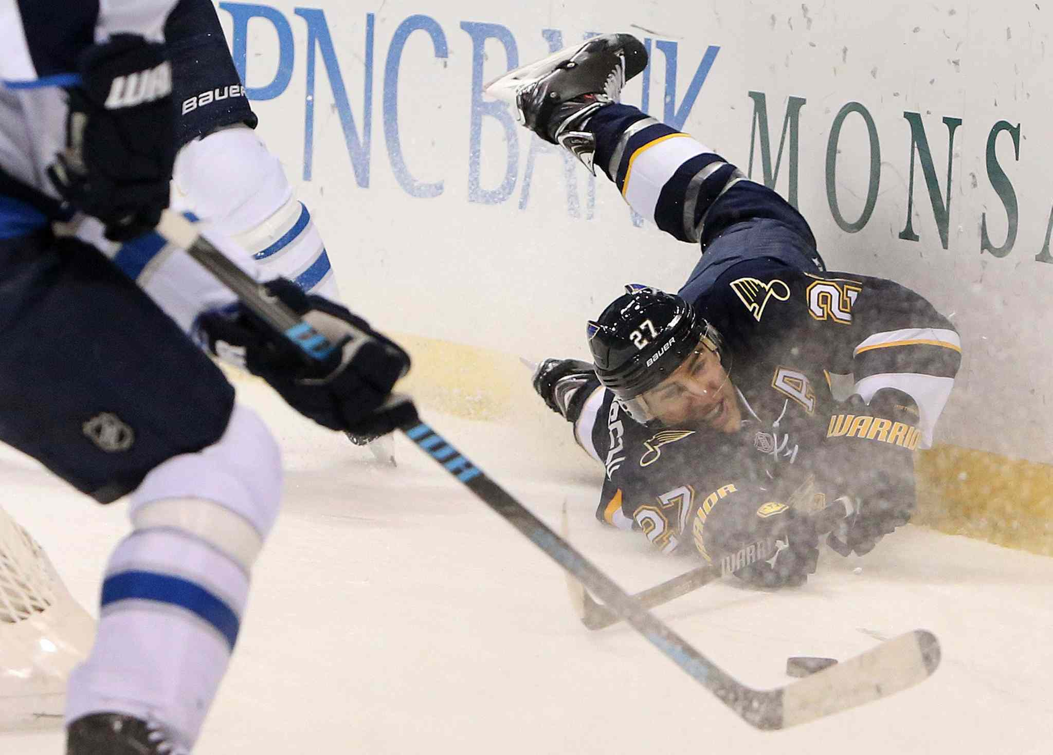 Alex Pietrangelo of the St. Louis Blues stretches for the puck as he slides into the boards during Saturday's game against the Winnipeg Jets.