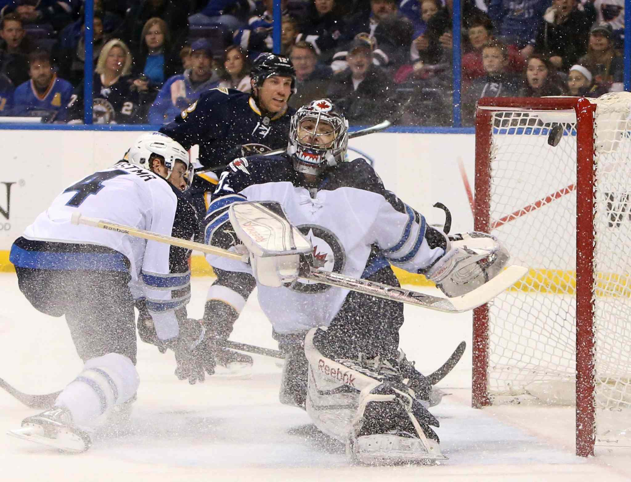 Derk Roy, back, scores against Winnipeg Jets' goalie Al Montoya on Saturday in St. Louis.
