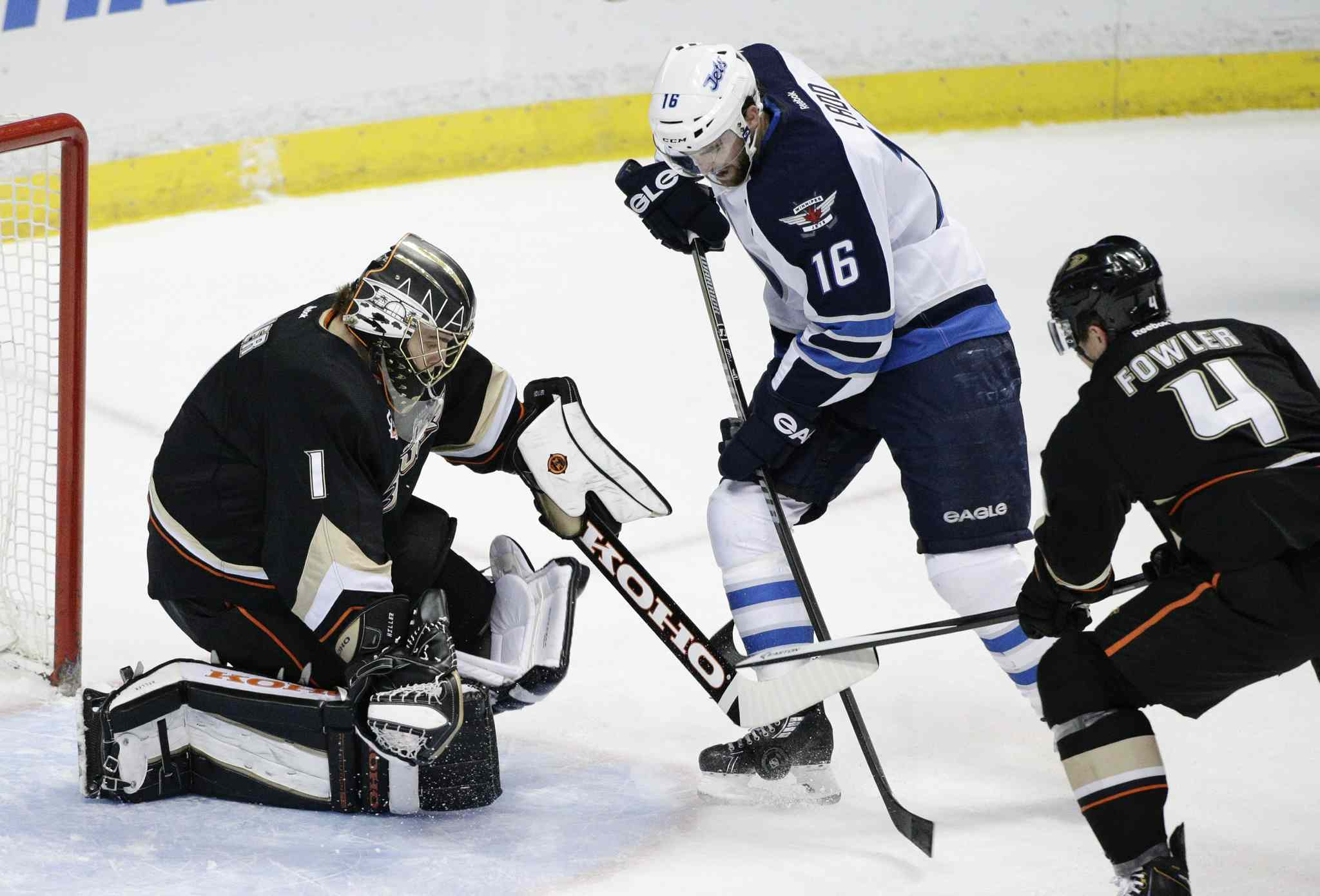 Winnipeg Jets' Andrew Ladd (16) tries to score against Anaheim Ducks' goalie Jonas Hiller, left, as the Ducks' Cam Fowler defends during first period in Anaheim Tuesday.