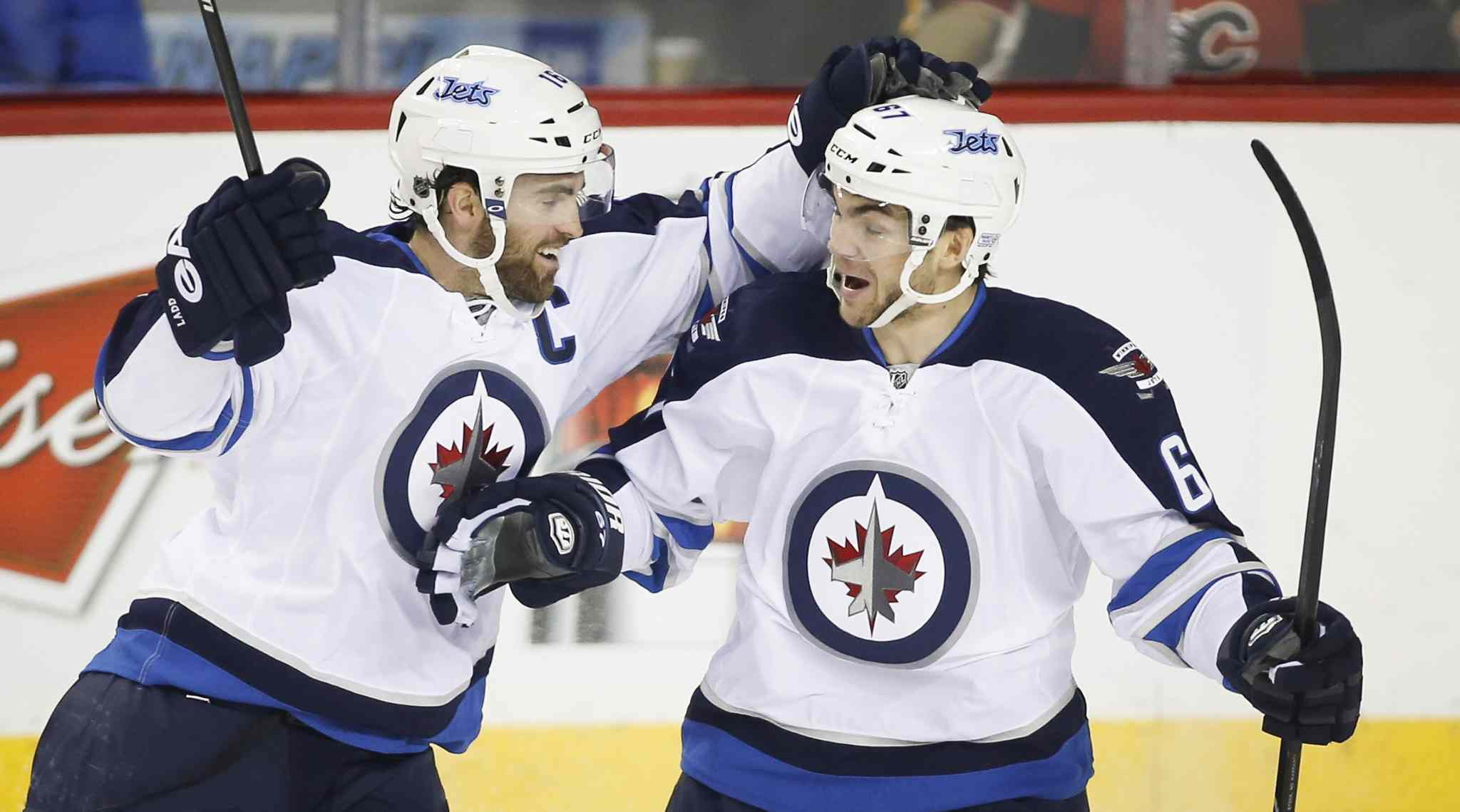 Winnipeg Jets' Michael Frolik, left, celebrates his assist with teammate Andrew Ladd during first period NHL hockey action against the Calgary Flames in Calgary Thursday.
