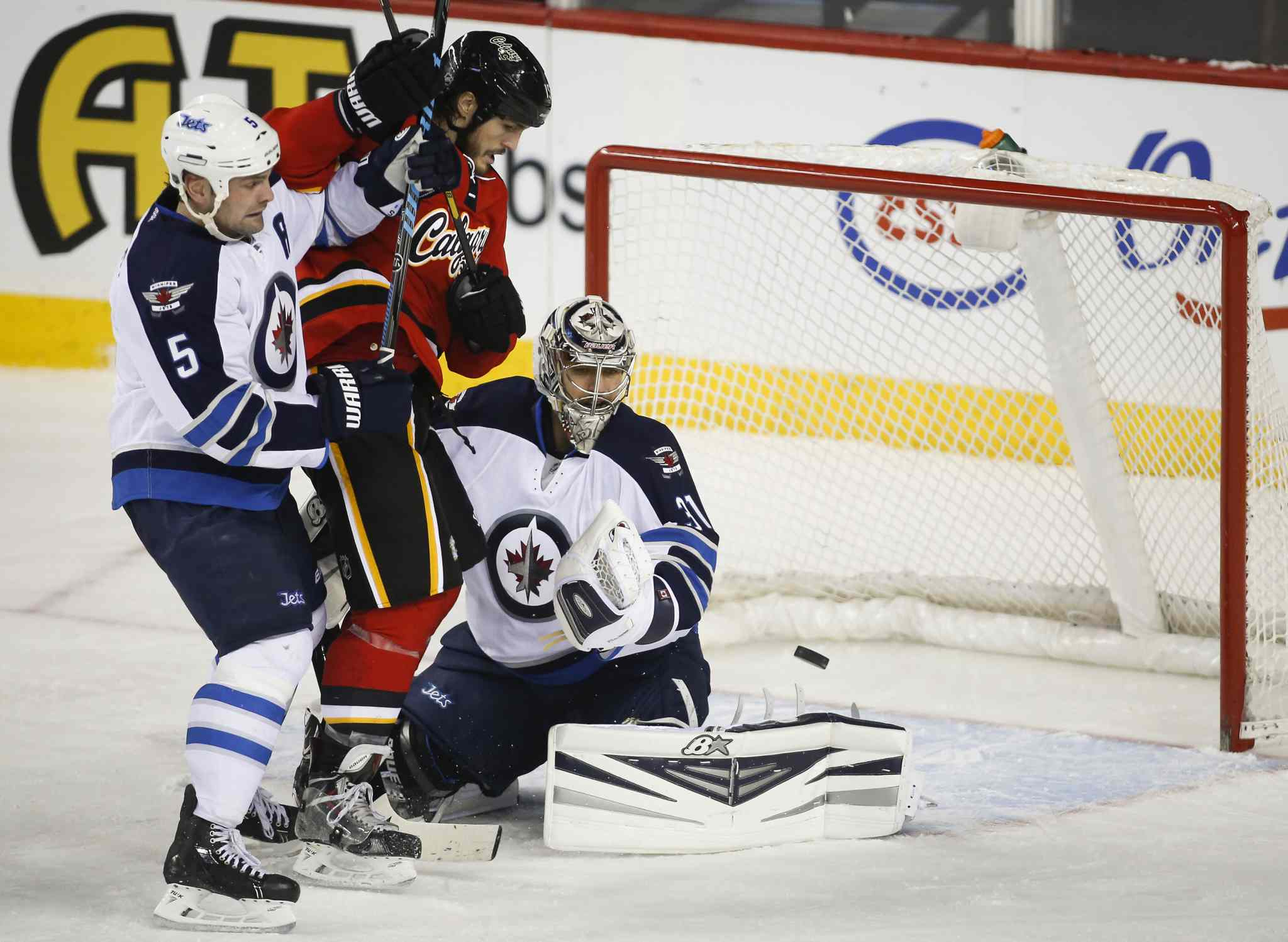 Winnipeg Jets' goalie Ondrej Pavelec, right, watches a rebound as teammate Mark Stuart checks Calgary Flames' Kevin Westgarth in the second period Thursday.