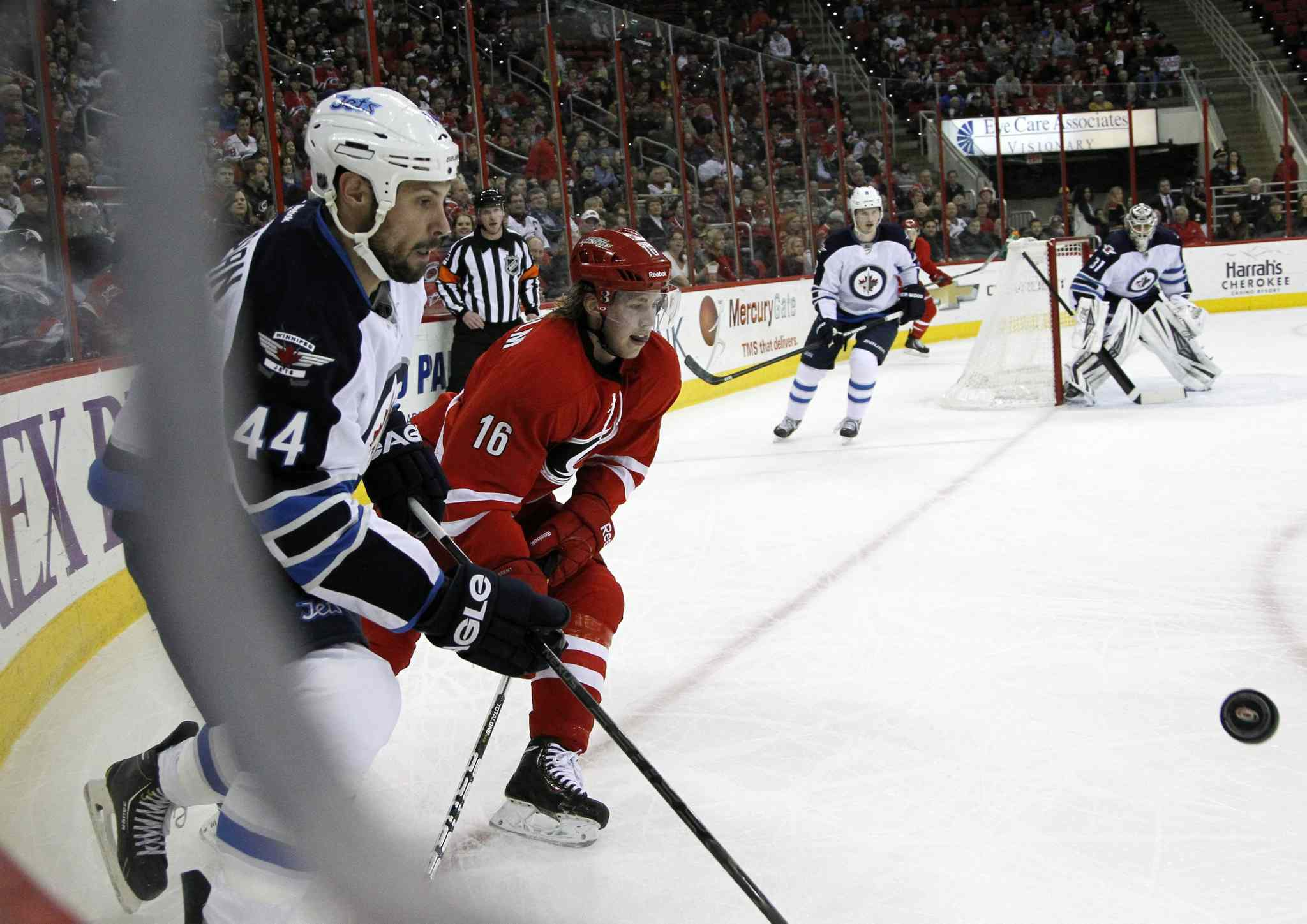 Winnipeg Jets' Zach Bogosian (44) and Carolina Hurricanes' Elias Lindholm (16) go for the puck during the first period at the PNC Arena in Raleigh, N.C., on Tuesday.