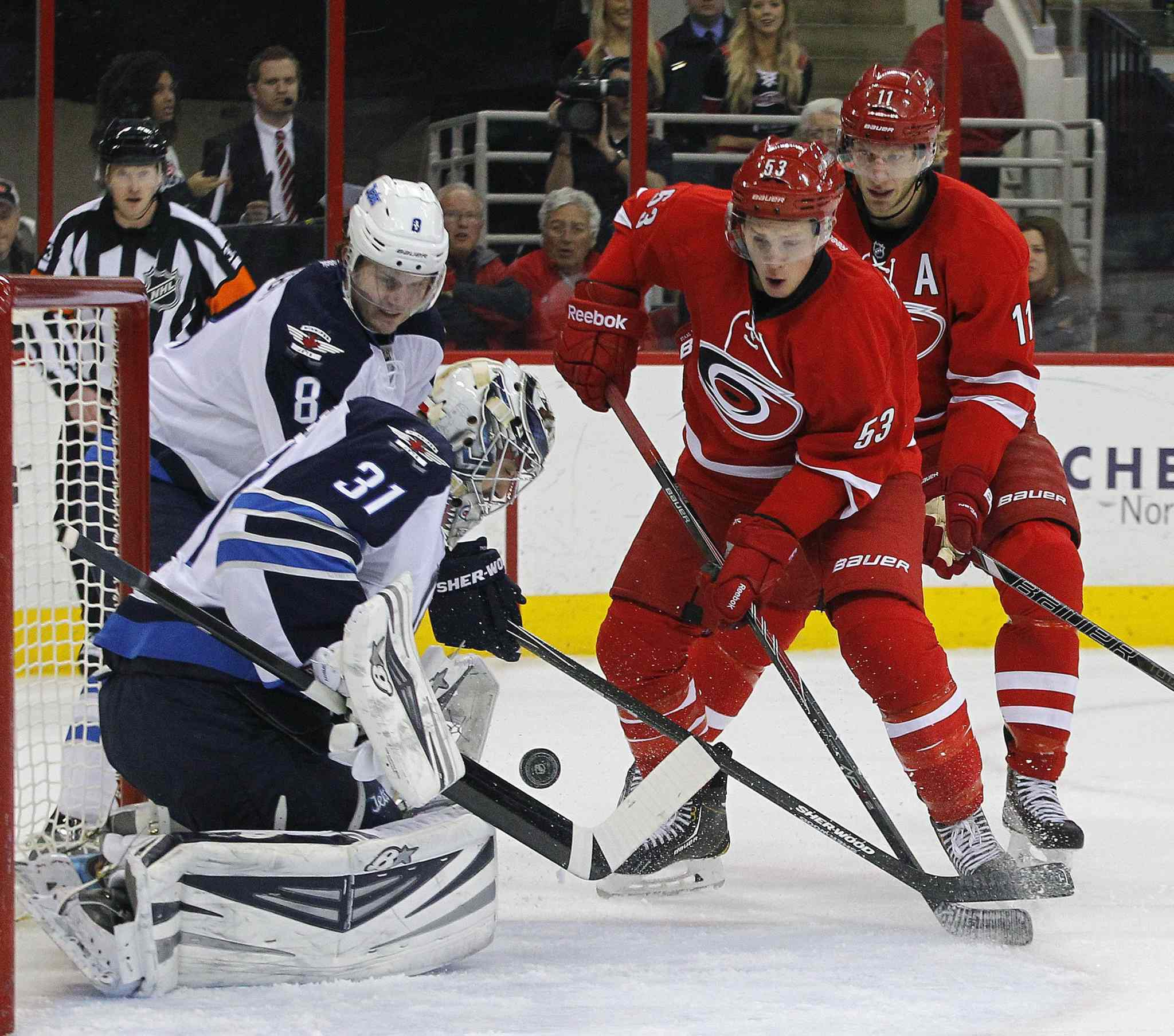Carolina Hurricanes' Jeff Skinner (53) and Eric Staal (12) work against Winnipeg Jets' Jacob Trouba (8) and Ondrej Pavelec (31) during the first period at the PNC Arena in Raleigh, N.C., on Tuesday, Feb. 4, 2014.