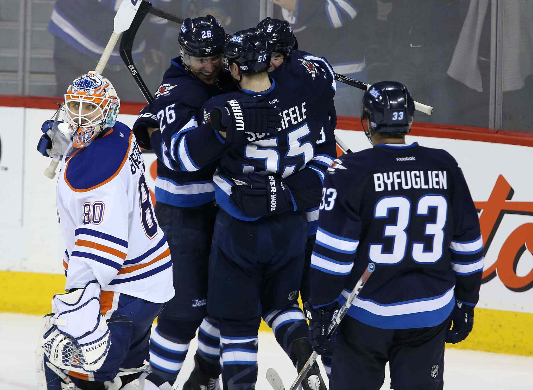 Edmonton Oilers' goaltender Ilya Bryzgalov (80) looks on as the Winnipeg Jets' Blake Wheeler (26), Mark Scheifele (55), Jacob Trouba (8) and Dustin Byfuglien (33) celebrate Trouba's game-winning goal in overtime to beat the Edmonton Oilers 3-2 in Winnipeg Saturday.