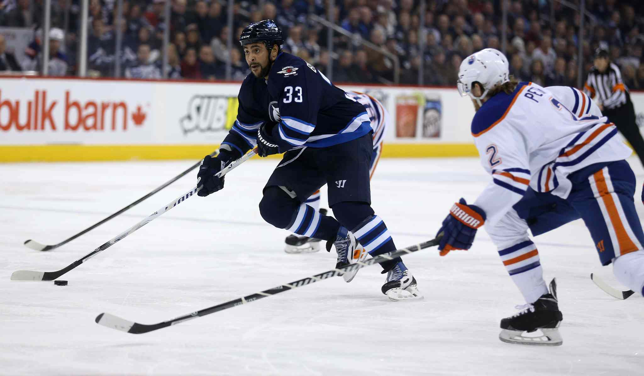 Winnipeg Jets' Dustin Byfuglien (33) drives to the net past Edmonton Oilers' Jeff Petry (2) during second period NHL hockey action at MTS Centre in Winnipeg on Saturday.