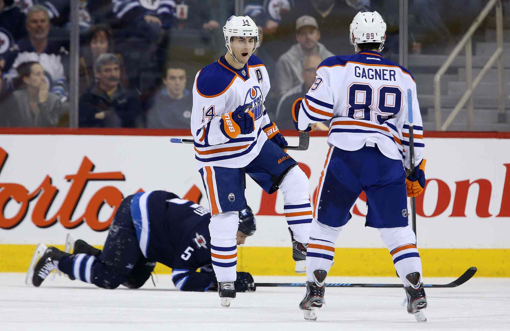 Edmonton Oilers' Jordan Eberle (14) celebrates with Sam Gagner (89) after scoring against the Winnipeg Jets during NHL hockey action at MTS Centre in Winnipeg Saturday.