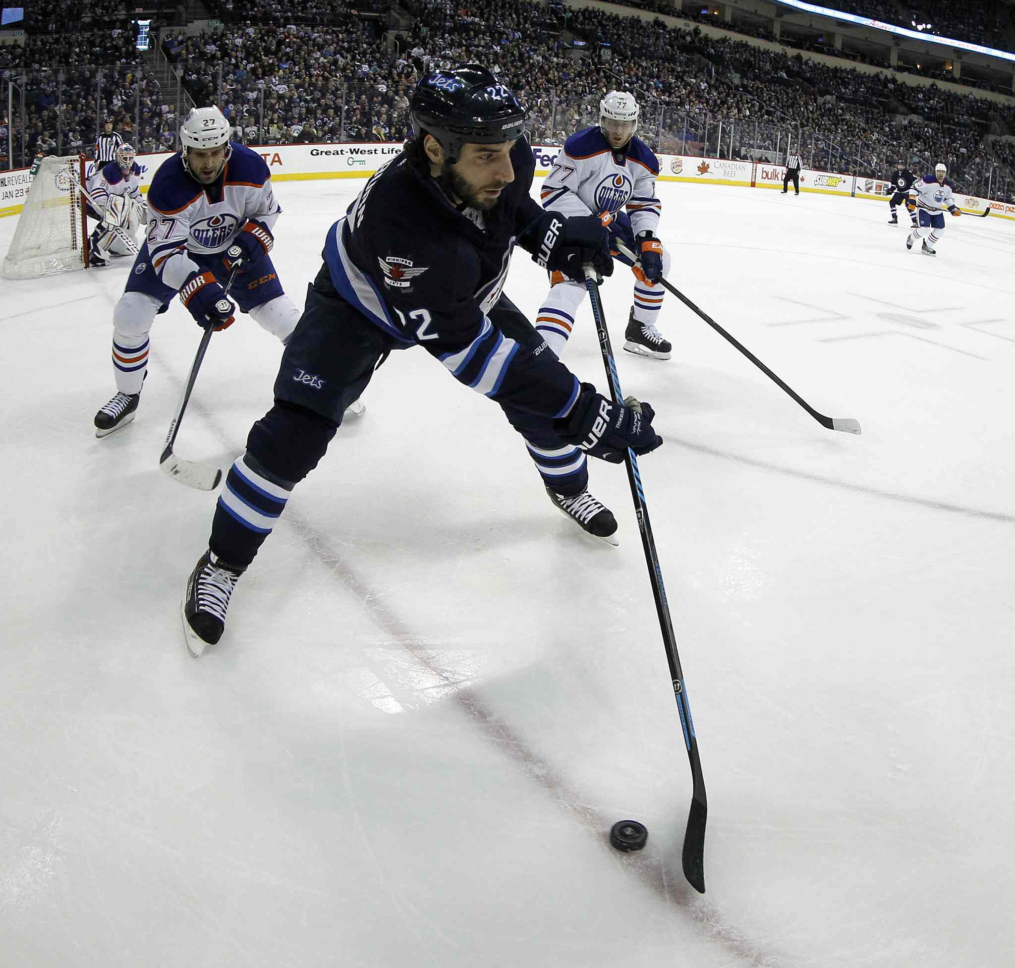 Winnipeg Jets' Chris Thorburn (22) carries the puck in front of Edmonton Oilers' Boyd Gordon (27) and Anton Belov (77) during second period in Winnipeg Saturday.