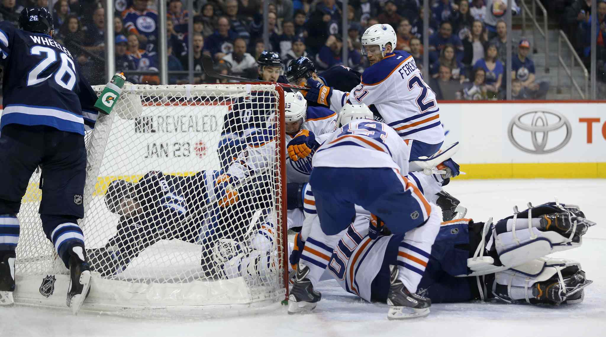 Winnipeg Jets' Jacob Trouba (8) ends up in the net past Edmonton Oilers' goaltender Ilya Bryzgalov (80) during the second period of Saturday's NHL game in Winnipeg.