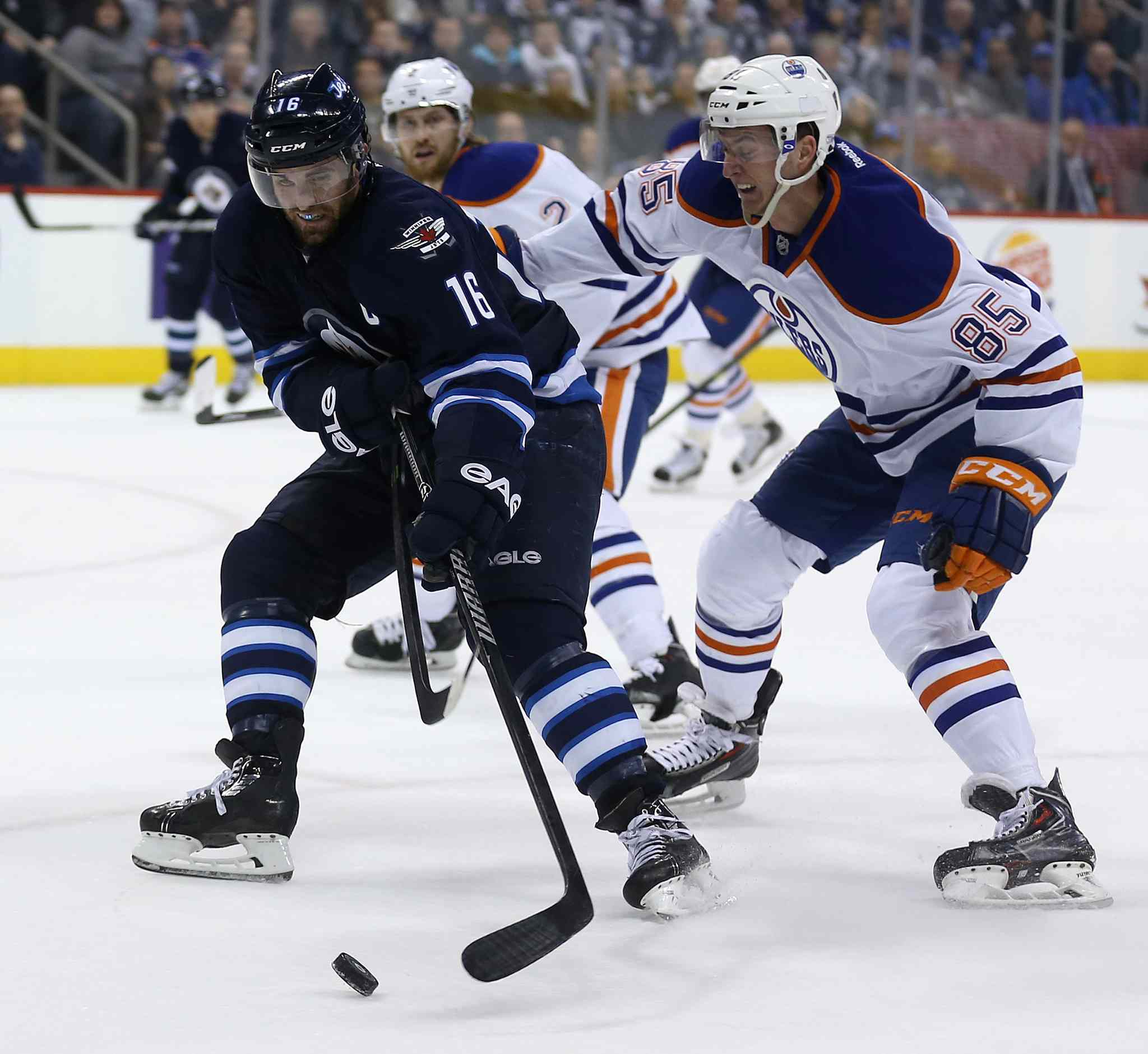 Winnipeg Jets' Andrew Ladd (16) drives past Edmonton Oilers' Martin Marincin (85) during second-period NHL play in Winnipeg Saturday afternoon.