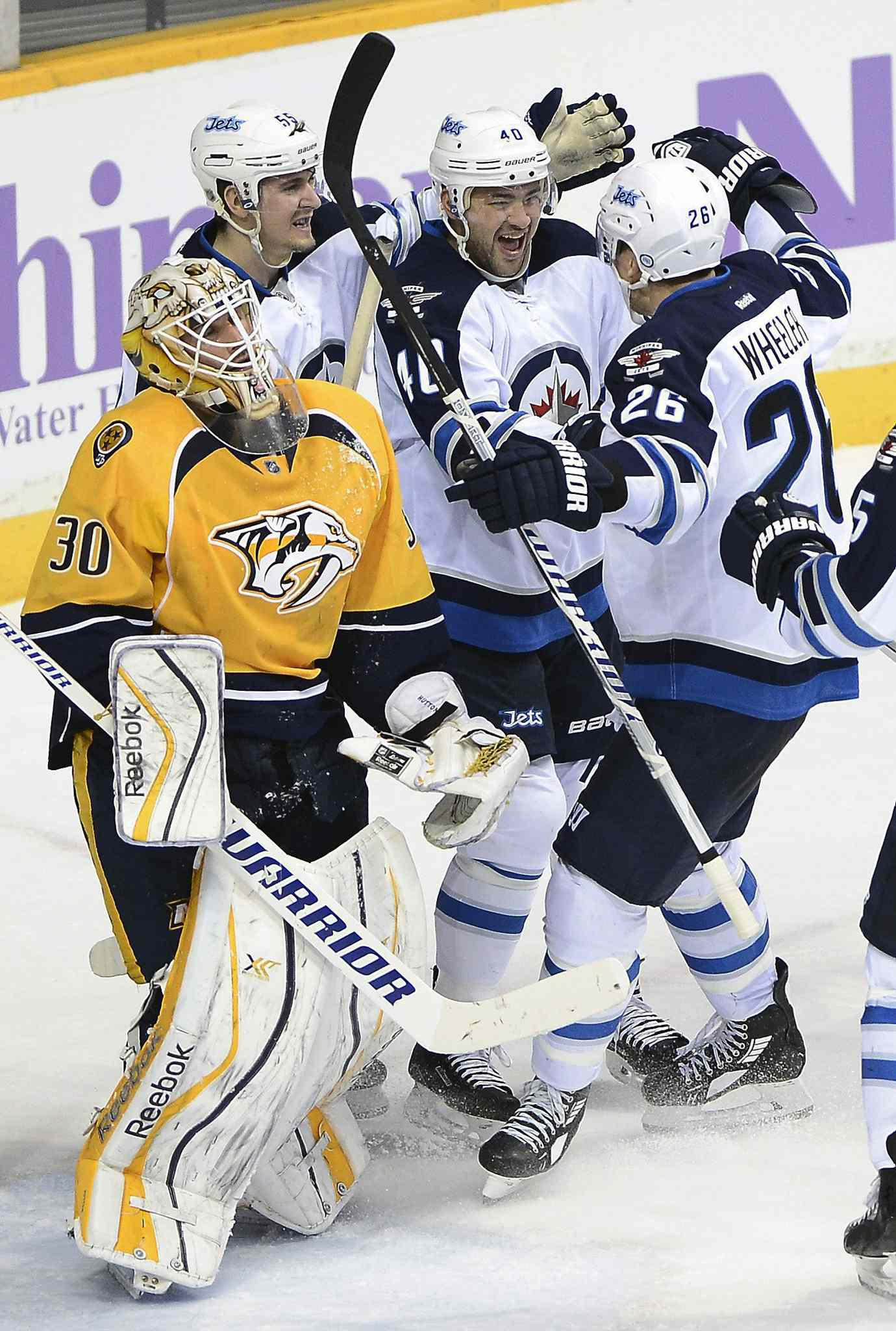 Winnipeg Jets' right wing Devin Setoguchi (40) celebrates with Mark Scheifele (55) and Blake Wheeler (26) after Setoguchi scored a third-period goal against Nashville Predators' goalie Carter Hutton (30). The Jets won 3-1.