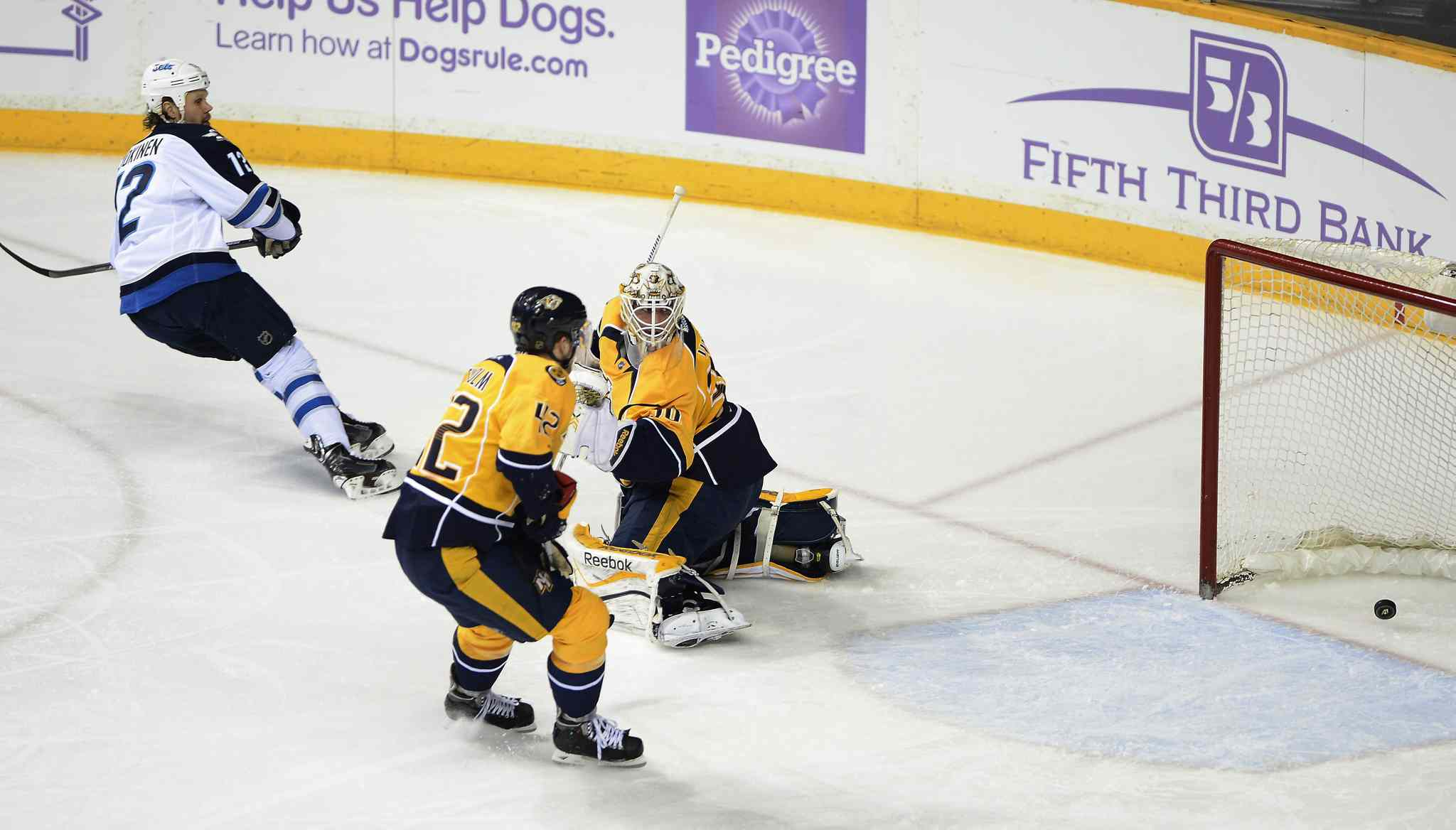 Winnipeg Jets' centre Olli Jokinen (12) scores a second-period goal against Nashville Predators' defenseman Mattias Ekholm (42) and goalie Carter Hutton (30) in Nashville Saturday.