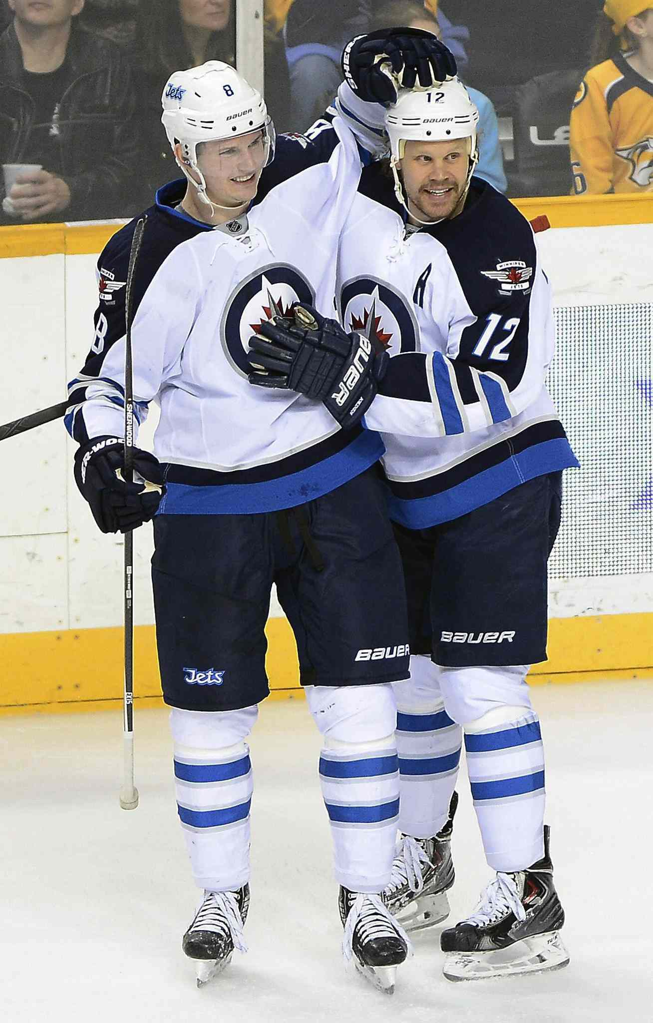 Winnipeg Jets' defenseman Jacob Trouba (8) celebrates with Olli Jokinen (12) after Jokinen scored a second-period goal against the Nashville Predators on Saturday.