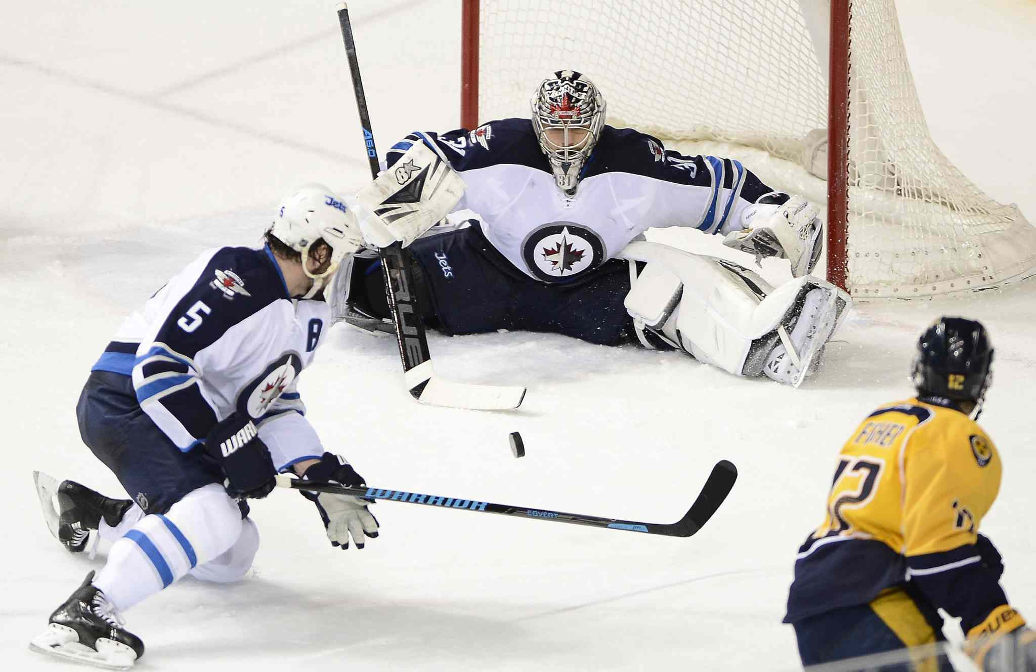 Winnipeg Jets' goalie Ondrej Pavelec (31) blocks a third-period shot from Nashville Predators' forward Mike Fisher (12) as Jets' defenseman Mark Stuart (5) tries to clear the puck.