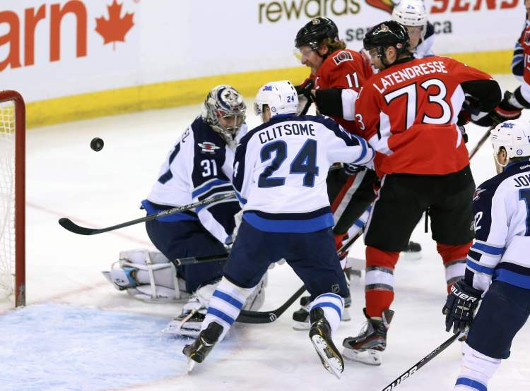 Ottawa Senators' Daniel Alfredsson (11) and Guillaume Latendresse watch as the puck sails past Winnipeg Jets goaltender Ondrej Pavelec and defenceman Grant Clitsome during first-period NHL action in Ottawa Sunday.