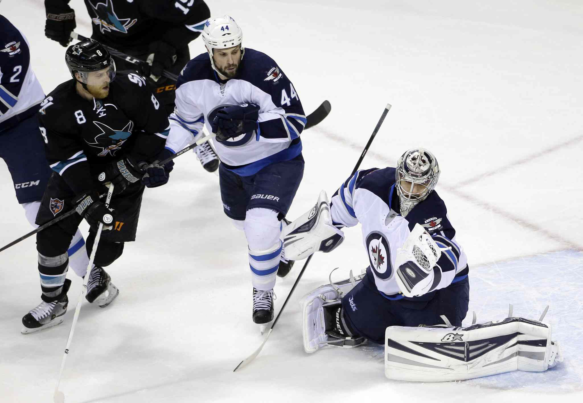 Winnipeg Jets' goalie Ondrej Pavelec, right, stops a shot next to teammate Zach Bogosian (44) and San Jose Sharks' Joe Pavelski (8) during the first period of Thursday's game.