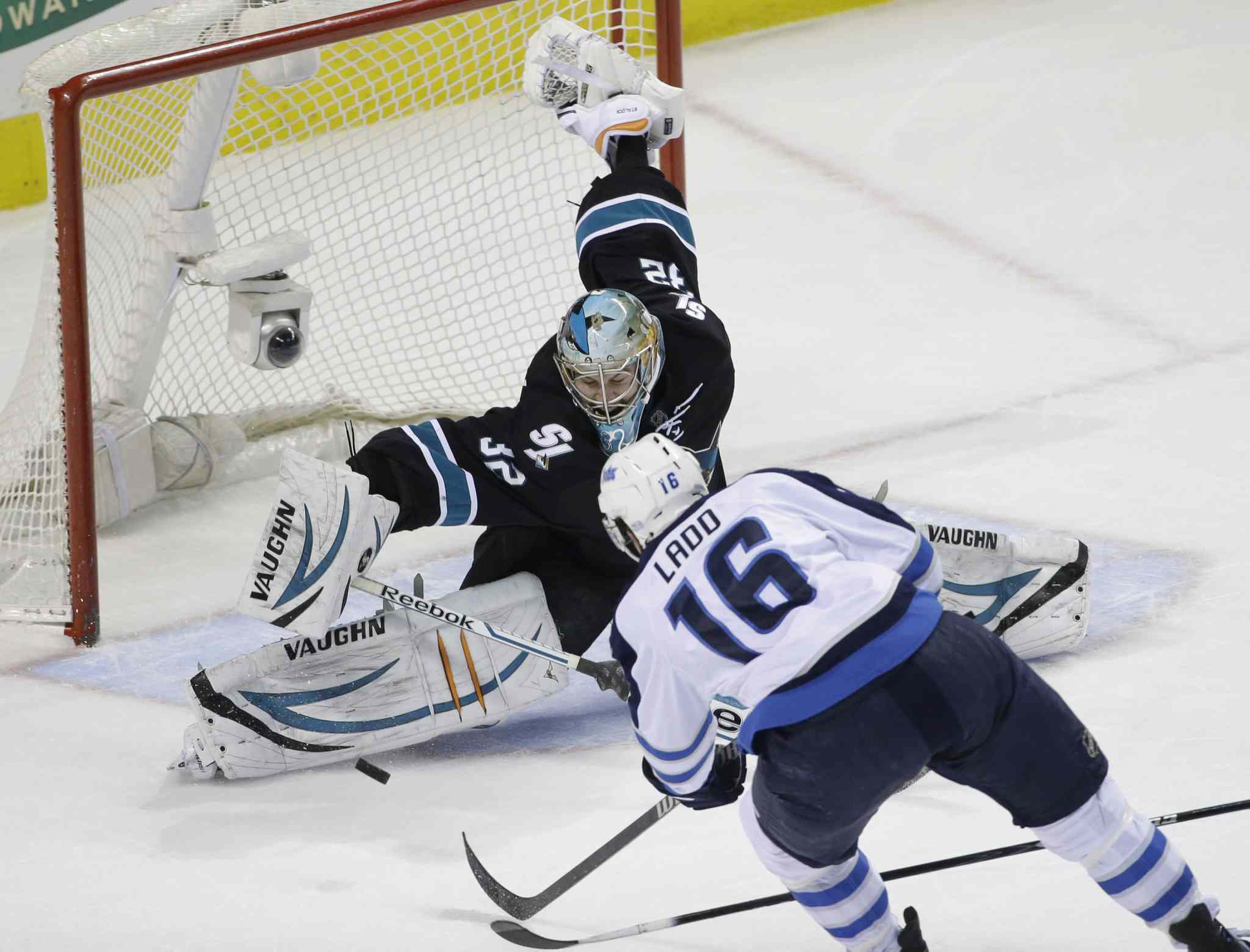 San Jose Sharks' goalie Alex Stalock (32) stops a shot by Winnipeg Jets' Andrew Ladd (16) during the first period Thursday's NHL hockey game in San Jose, Calif.