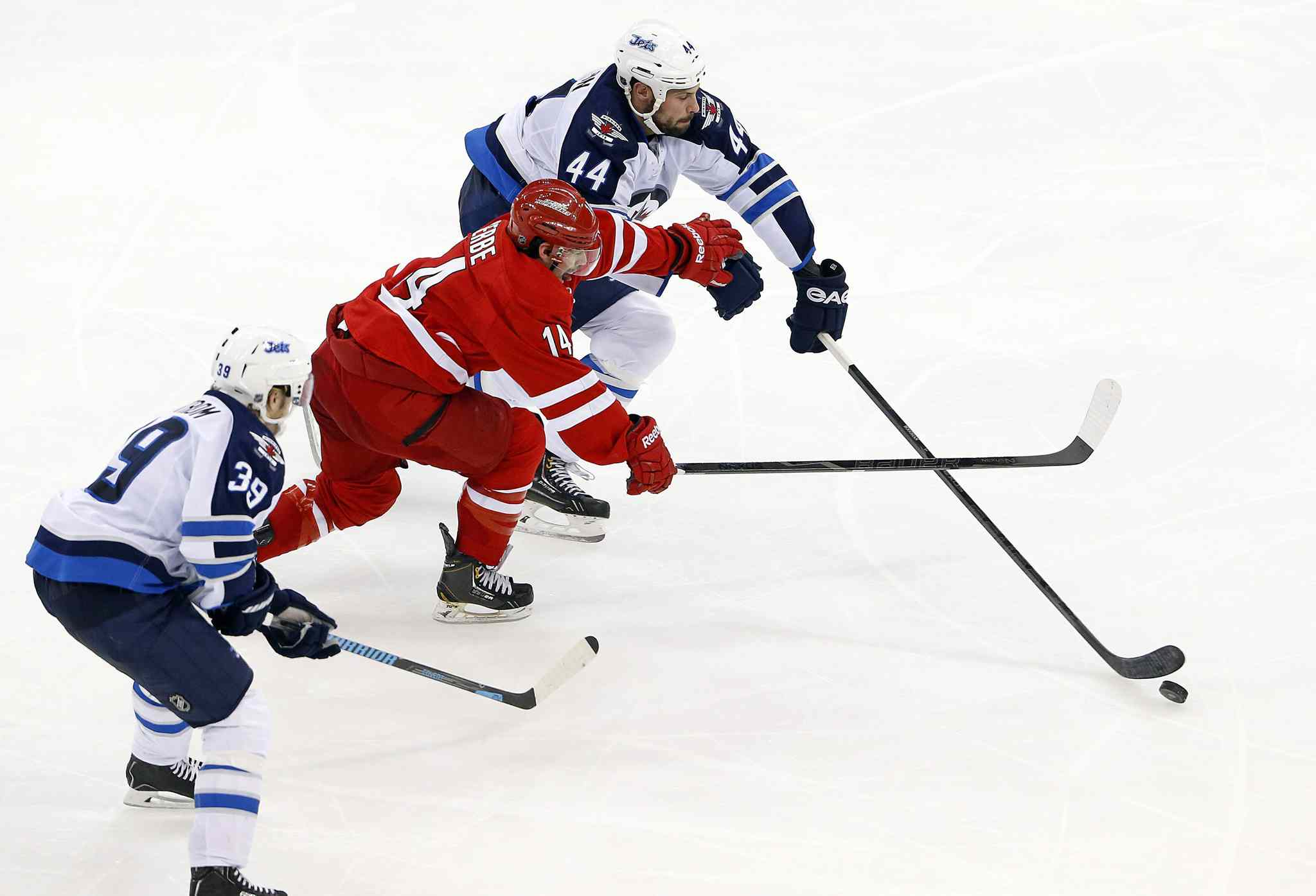 Carolina Hurricanes' Nathan Gerbe (14) tries to split the defense of Winnipeg Jets' Zach Bogosian (44) and Tobias Enstrom (39) of Sweden, during the third period of Tuesday's game.