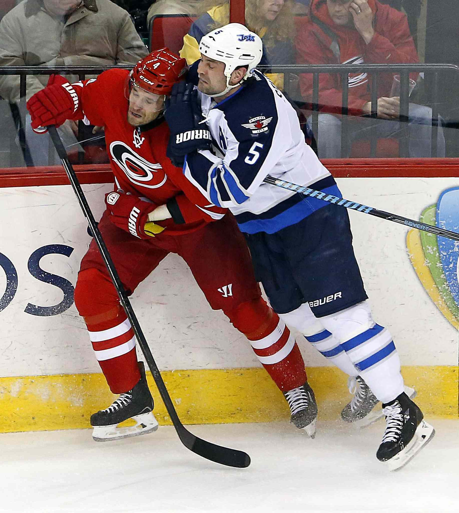 Winnipeg Jets' Mark Stuart (5) checks Carolina Hurricanes' Andrej Sekera (4) into the boards during the third period of Tuesday's game.