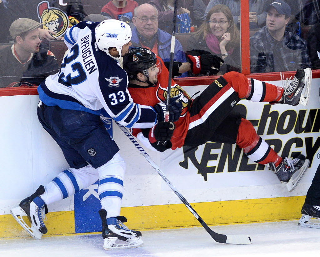 Ottawa Senators' Cory Conacher gets roughed up by Winnipeg Jets' Dustin Byfuglien during second period in Ottawa Thursday.  (Sean Kilpatrick / The Canadian Press)