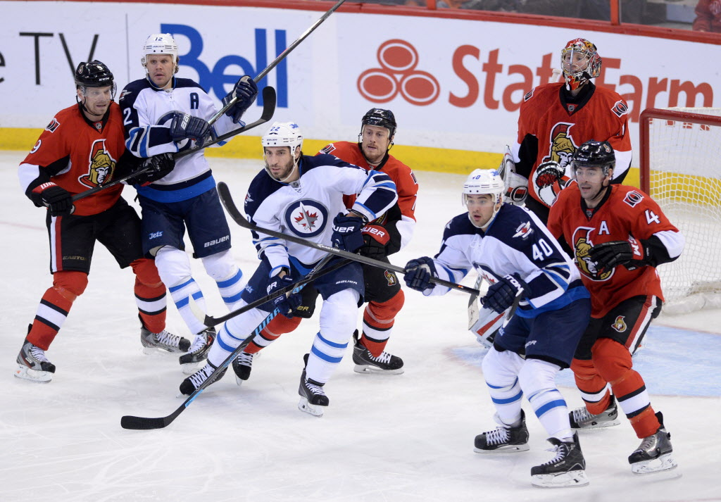 Ottawa Senators' Craig Anderson tries to keep his eye on the puck as teammates Milan Michalek, left to right, Joe Corvo, and Chris Phillips defend against Winnipeg Jets' Olli Jokinen, left to right, Chris Thorburn, and Devin Setoguchi during the third period Thursday.