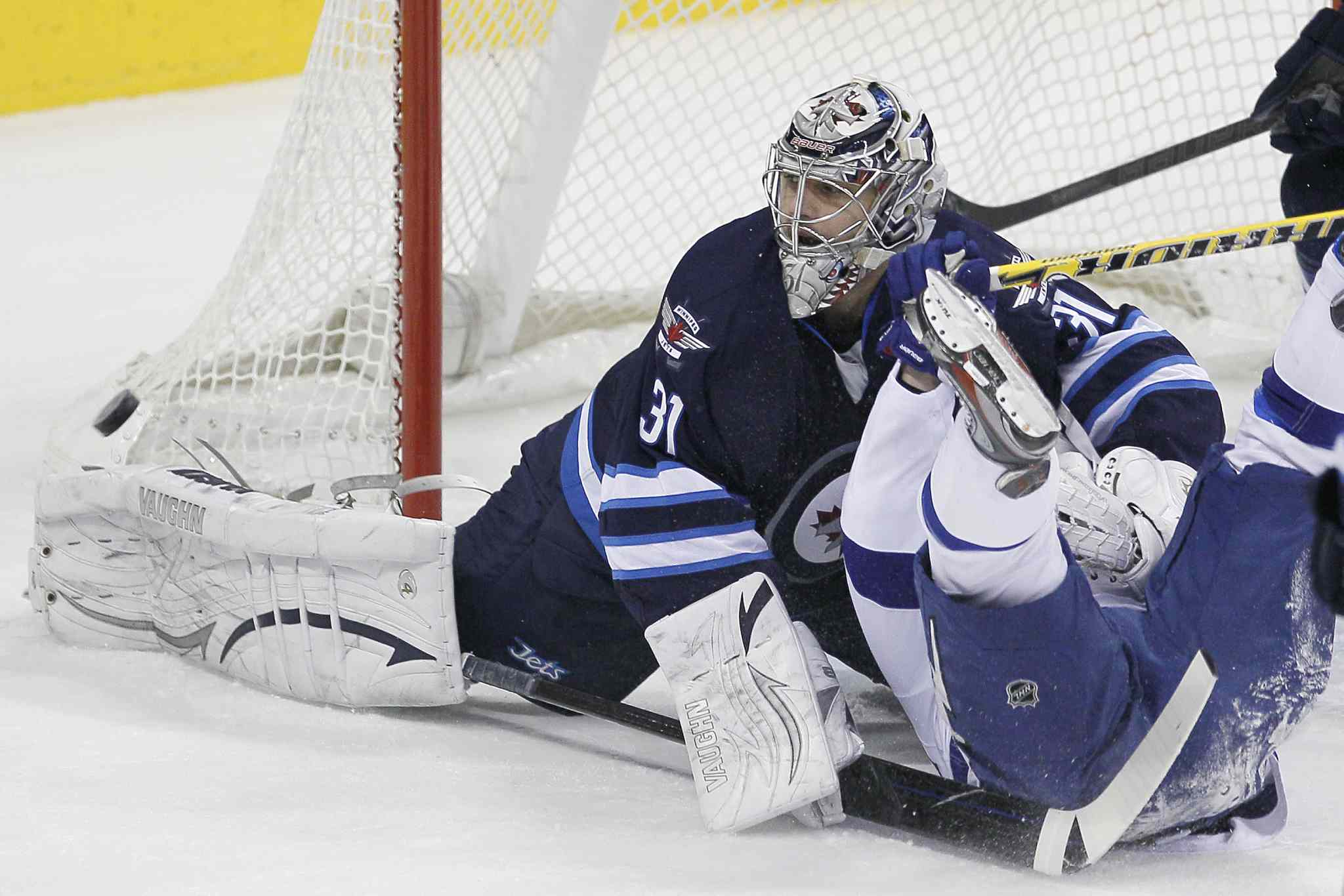 Winnipeg Jets' goaltender Ondrej Pavelec (31) saves the shot as he gets tangled up with Tampa Bay Lightning's Martin St. Louis (26) during first period NHL action in Winnipeg Tuesday.