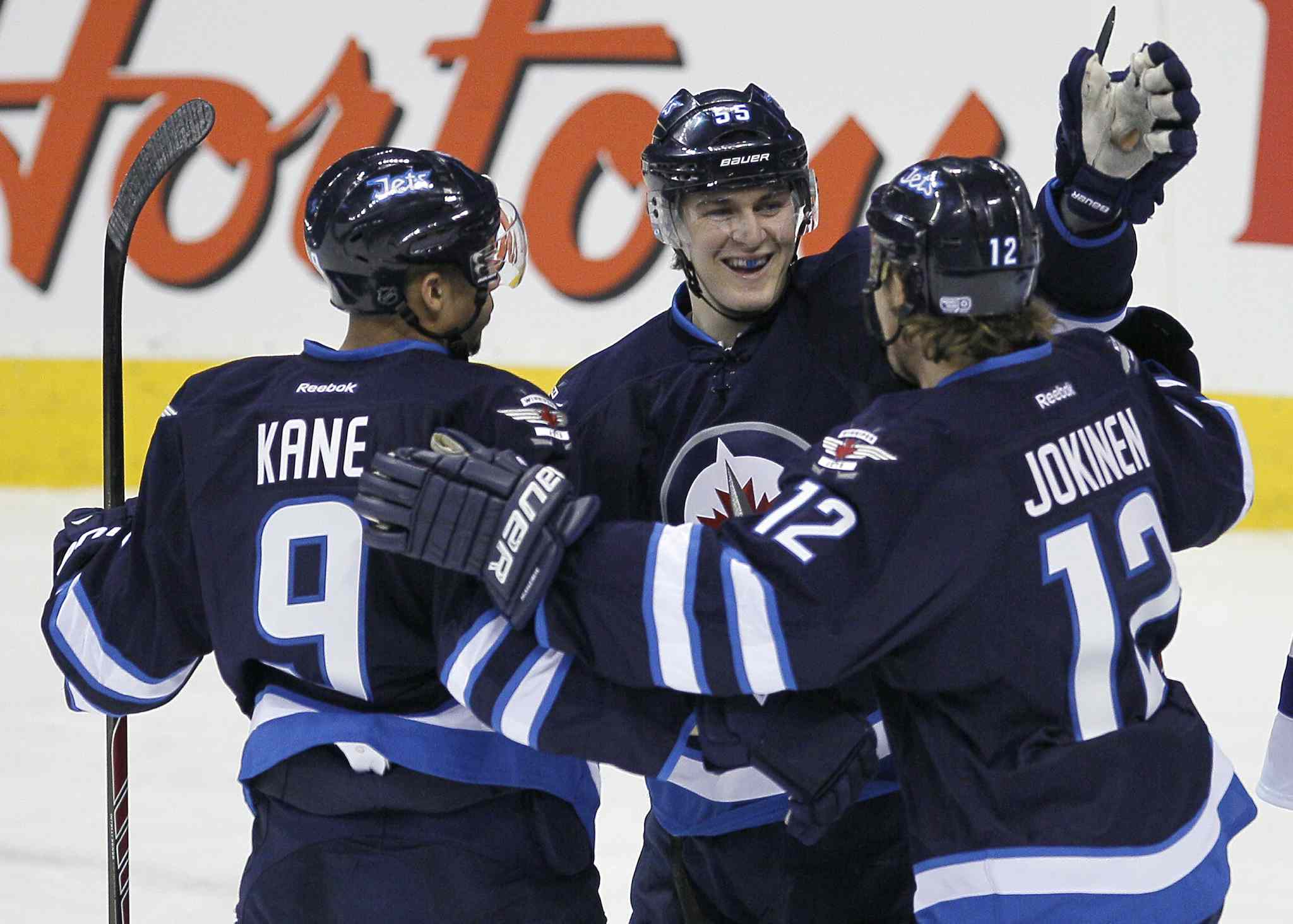Winnipeg Jets' Evander Kane (9), Mark Scheifele (55) and Olli Jokinen (12) celebrate Jokinen's goal on Tampa Bay Lightning's goaltender Anders Lindback (39) in the first period of Tuesday's game.