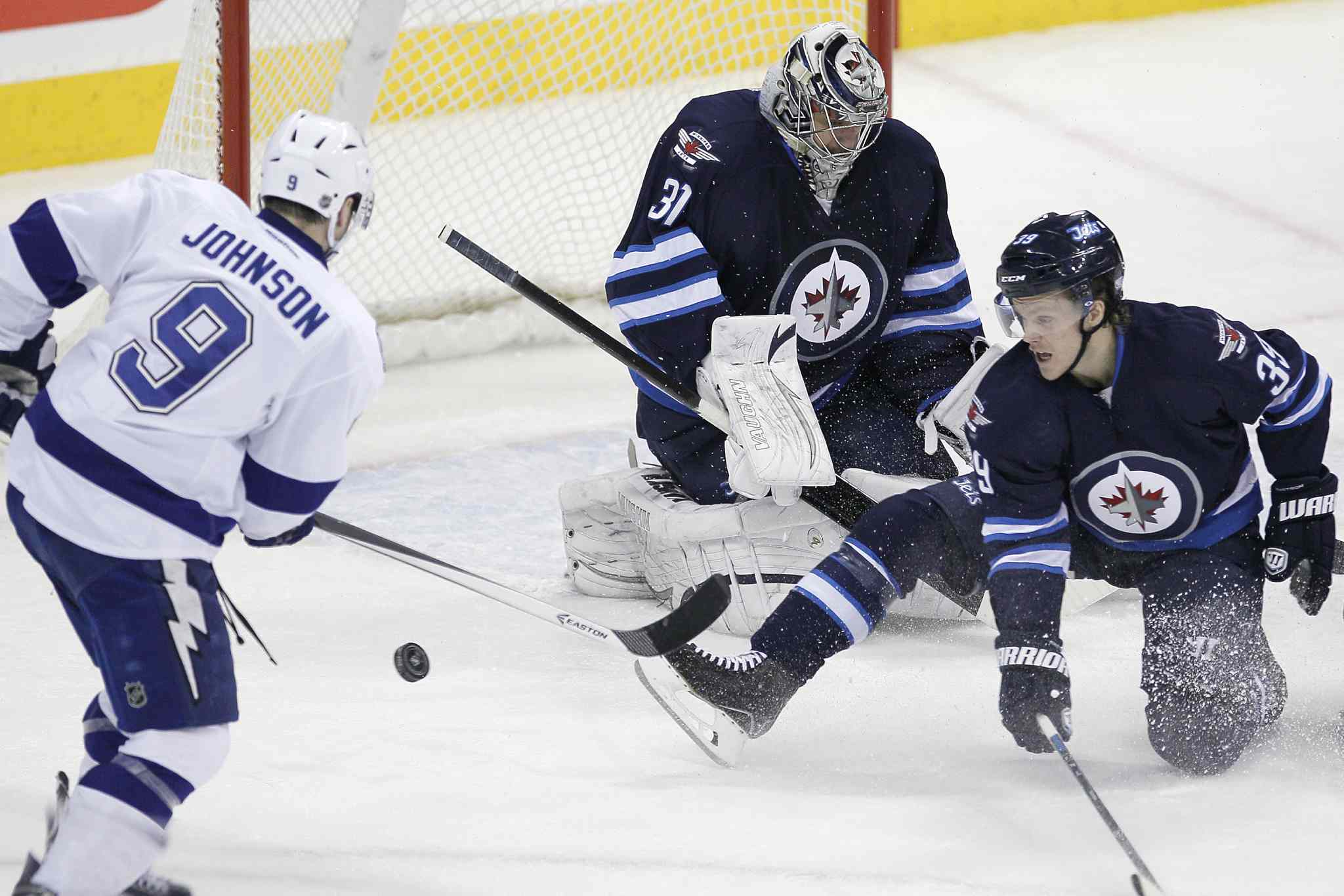 Winnipeg Jets' Tobias Enstrom (39) blocks the first-period shot by Tampa Bay Lightning's Tyler Johnson (9) in front of Jets' goaltender Ondrej Pavelec (31).