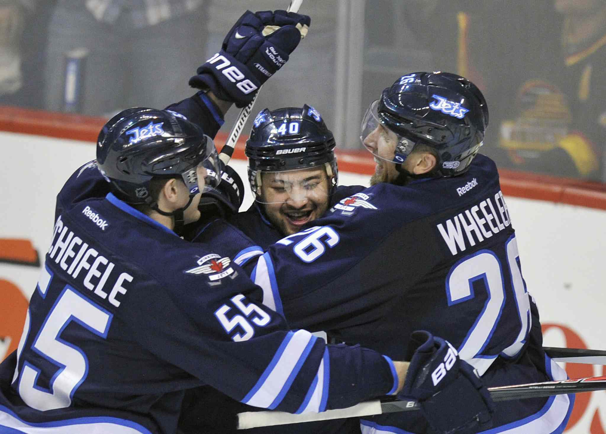 Winnipeg Jets' Devin Setoguchi is congratulated by teammates Mark Scheifele, left, and Blake Wheeler after scoring the game-winning goal against the Vancouver Canucks in Winnipeg Friday night. The Jets beat the Canucks 4-3.