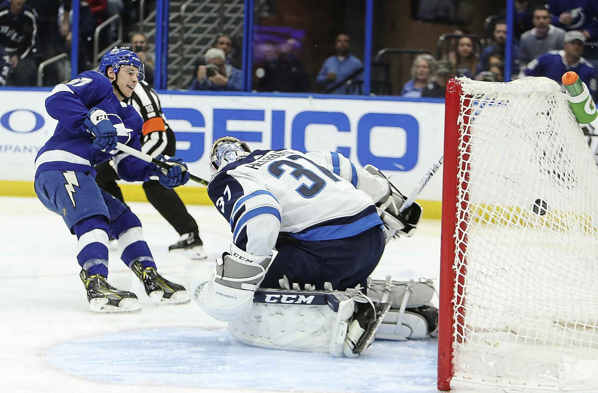 The Tampa Bay Lightning's Yanni Gourde beats Winnipeg Jets goaltender Connor Hellebuyck in the first period.