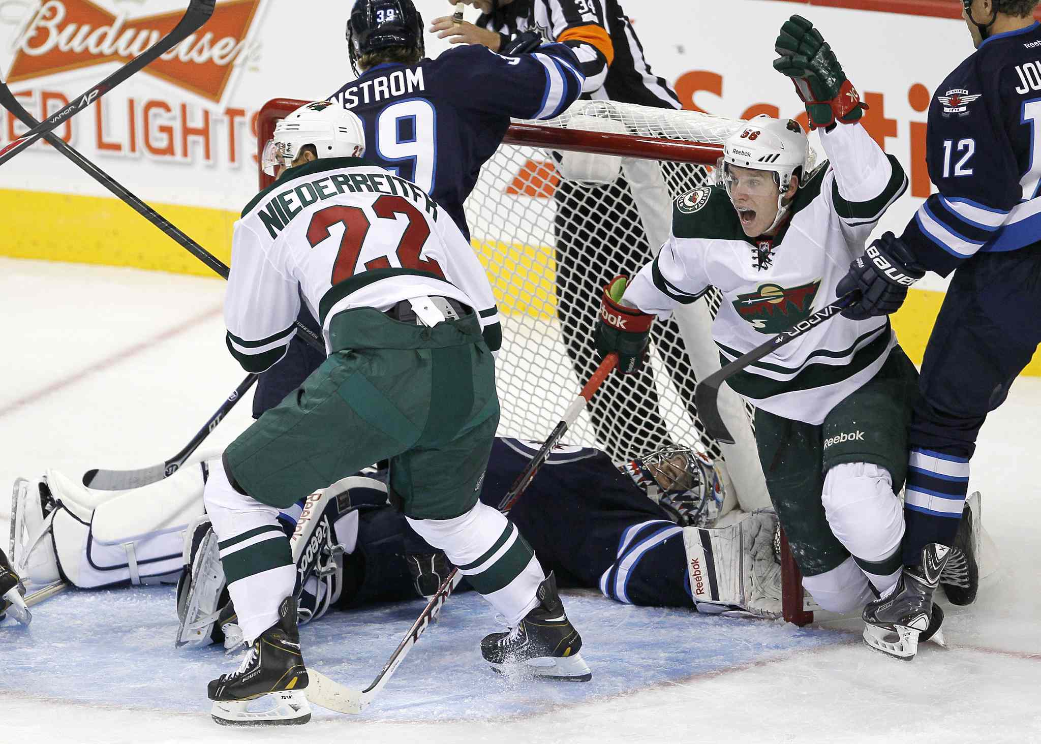 Minnesota Wild's Erik Haula (56) and Nino Niederreiter (22) celebrate a goal by teammate Mathew Dumba (not shown) against Winnipeg Jets goaltender Al Montoya during the first period.