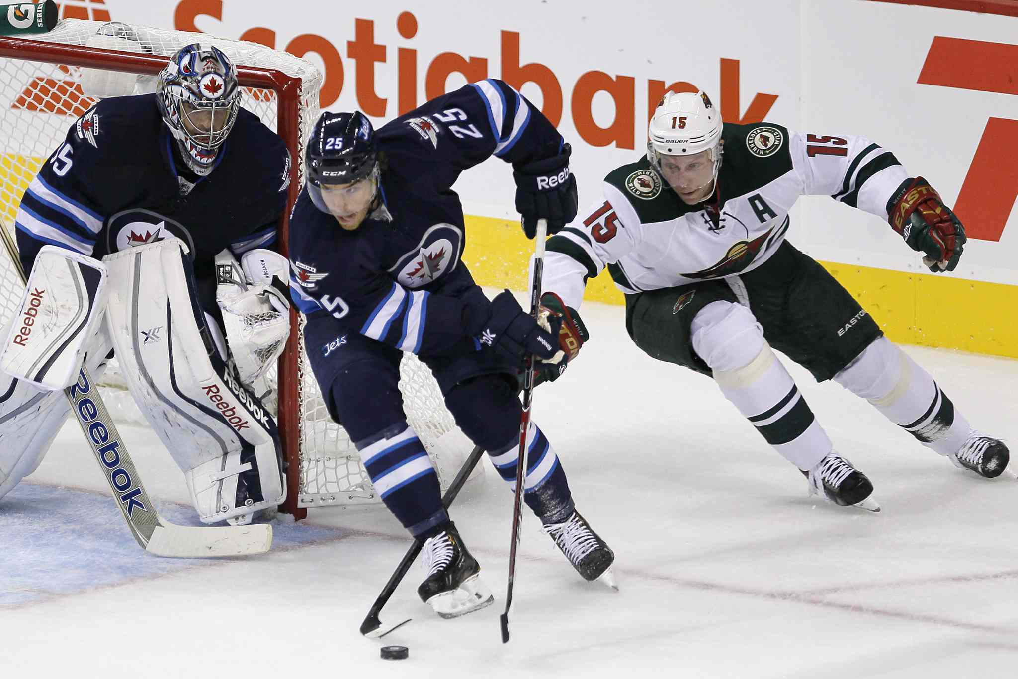 Dany Heatley (right) chases down Zach Redmond of the Winnipeg Jets as goaltender Al Montoya looks on during the first period.