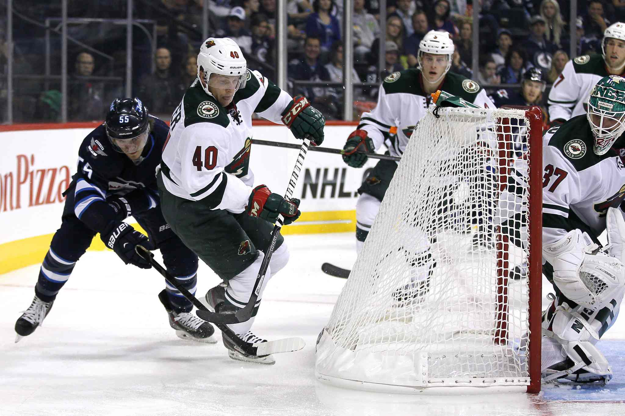 Winnipeg Jets' Mark Scheifele (left) and Minnesota Wild's Steven Kampfer (40) fight for the puck behind the Wild's net during the second period.