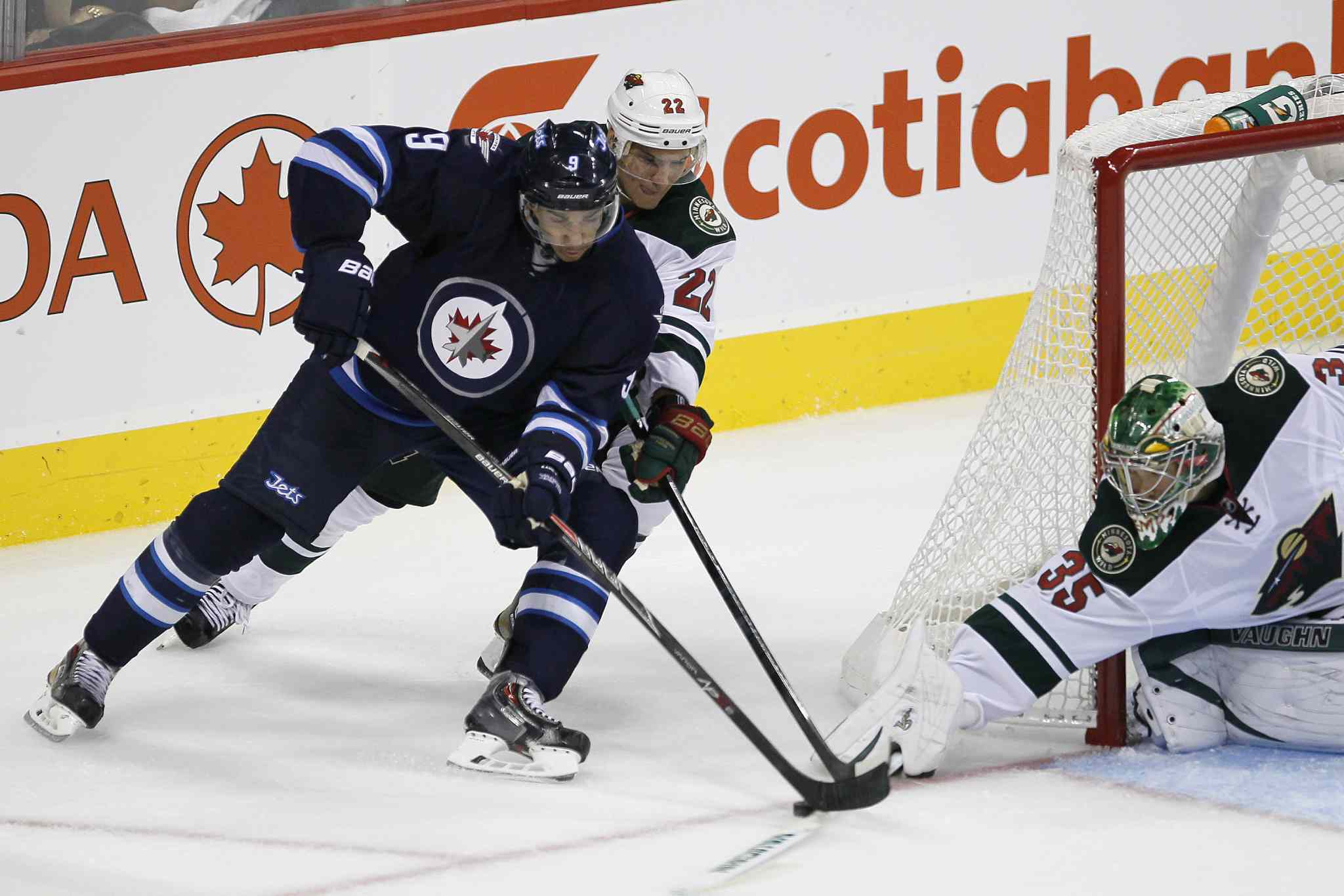 Minnesota Wild's Nino Niederreiter (22) and goaltender Darcy Kuemper (35) shut down Winnipeg Jets' Evander Kane (9) as he tries a wrap-around during the third period.